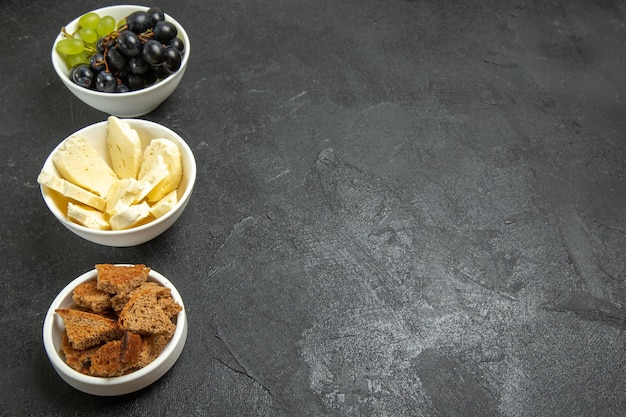 Vorderansicht frische trauben mit weißem käse und geschnittenem dunklem brot auf dem dunklen hintergrund essen gericht milchfrucht