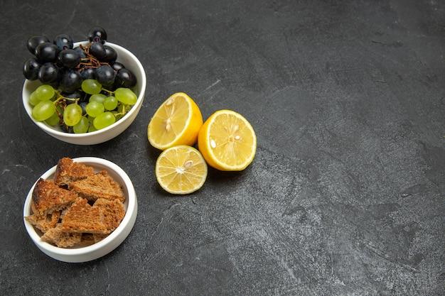 Vorderansicht frische trauben mit zitronenscheiben auf dem dunklen hintergrund obst reifes baumvitamin