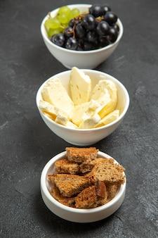 Vorderansicht frische, weiche trauben mit weißem käse und geschnittenem dunklem brot auf dem dunklen hintergrund