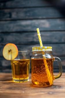 Vorderansicht frischer apfelsaft in dose und glas auf braunem holzschreibtisch fotococktail fruchtgetränk farbe
