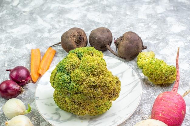 Vorderansicht frischer blumenkohl mit rüben-rettich-knoblauch und zwiebeln auf weißem schreibtisch reife salatmahlzeit farbfoto-essen