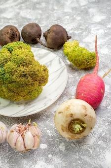 Vorderansicht frischer blumenkohl mit rüben-rettich-knoblauch und zwiebeln auf weißer oberfläche