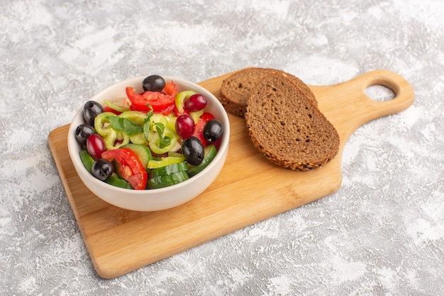 Vorderansicht frischer gemüsesalat mit geschnittenen gurkentomaten oliven- und weißkäse in teller mit brotlaib auf dem grauen schreibtisch gemüselebensmittelsalat mahlzeit