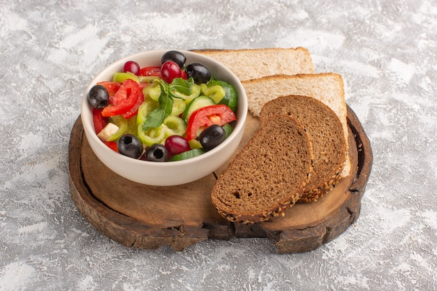 Vorderansicht frischer gemüsesalat mit geschnittenen gurkentomaten oliven- und weißkäse-innenplatte mit brot auf der grauen schreibtischgemüsesalat-salatmahlzeit