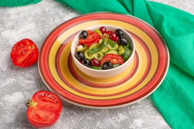 Vorderansicht frischer gemüsesalat mit geschnittenen gurkentomaten oliven- und weißkäse innerhalb platte auf der grauen oberfläche gemüselebensmittelsalatmahlzeit-foto