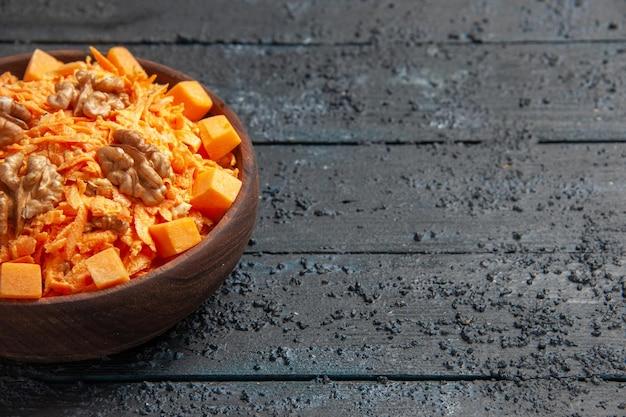 Vorderansicht frischer karottensalat geriebener salat mit walnüssen und knoblauch auf dem dunklen schreibtisch diätsalat gesundheit farbe nuss
