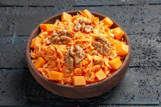 Vorderansicht frischer karottensalat geriebener salat mit walnüssen und knoblauch auf dunklem schreibtisch diät reife farbe salat gesundheit