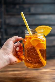 Vorderansicht frischer orangensaft im inneren kann auf dunklen barfrüchten farbfoto-cocktailgetränk
