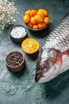 Vorderansicht frischer roher fisch mit kumquats auf dunkler oberfläche lebensmittel gesundheit wasser fisch farbe mahlzeit ozean diät salat pfeffer meeresfrüchte