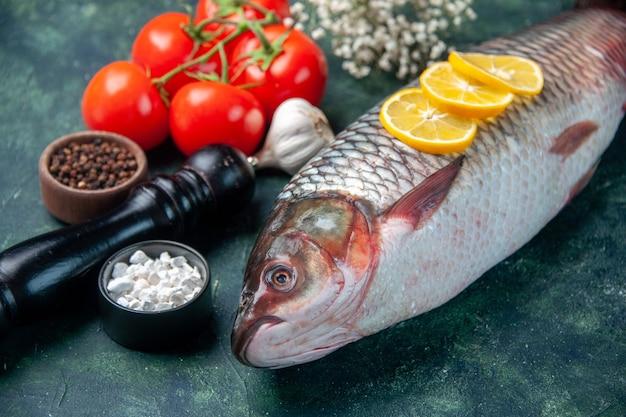 Vorderansicht frischer roher fisch mit tomaten und zitrone auf dunkelblauer oberfläche hai meeresfrüchte mahlzeit ozean horizontale abendessen nahrung tier wasser fleisch