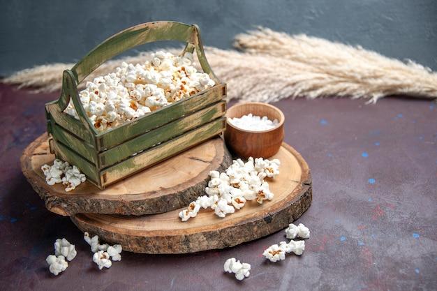 Vorderansicht frisches popcorn auf dem dunklen oberflächensnack-popcorn-mais-essen