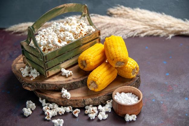 Vorderansicht frisches popcorn mit gelben hühneraugen auf dem dunklen oberflächen-snack-popcorn-mais-essen