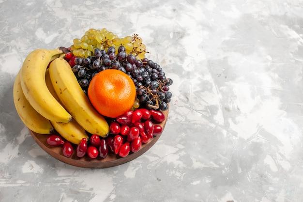 Vorderansicht fruchtzusammensetzung bananen hartriegel und trauben auf weißen schreibtischfrüchten beerenfrische vitamin
