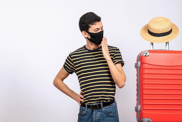 Vorderansicht gähnender junger tourist mit schwarzer maske, die nahe rotem koffer steht