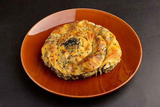 Vorderansicht gebäck mit fleisch köstliche teigmahlzeit in brauner platte auf dem dunklen schreibtisch ..