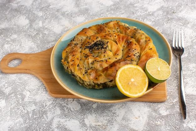Vorderansicht gebäck mit fleisch köstliche teigmahlzeit innerhalb platte mit zitrone auf hellem schreibtisch.