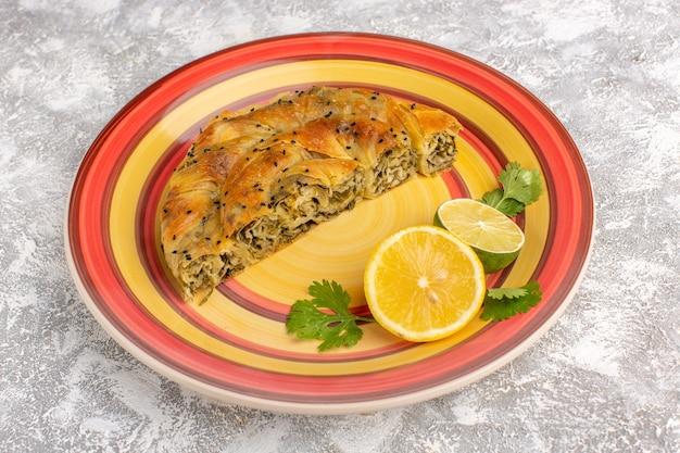 Vorderansicht gebäck mit fleisch köstliche teigmahlzeit innerhalb platte mit zitrone auf hellweißem schreibtisch geschnitten.
