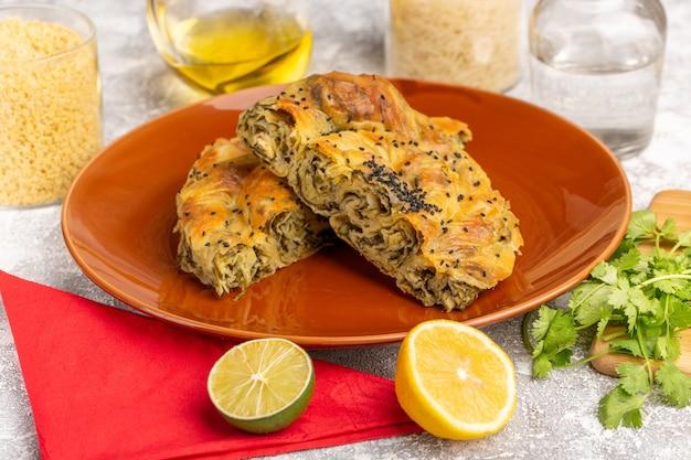 Vorderansicht gebäck mit fleisch köstliche teigmahlzeit innerhalb platte mit zitronenöl auf weißlicht schreibtisch.