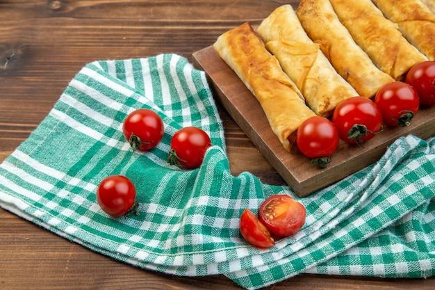 Vorderansicht gebratenes grüngebäck mit roten tomaten auf braunem hintergrund kuchenteigfleisch backen abendessen essen?
