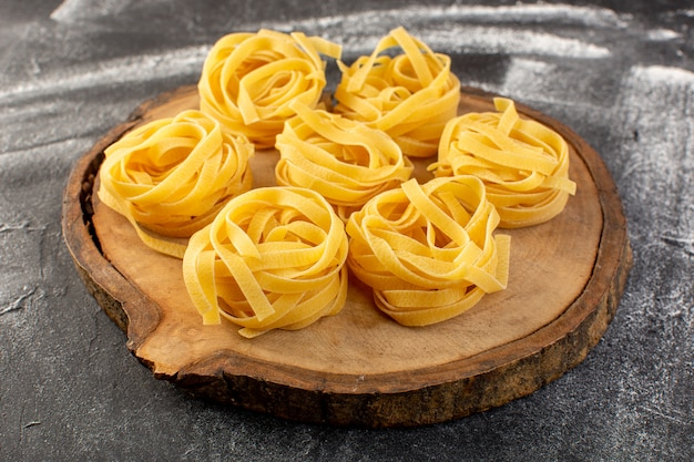 Vorderansicht geformte italienische nudeln in blütenform roh und gelb auf braun
