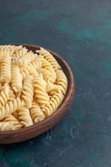 Vorderansicht geformte italienische pasta köstlich aussehende kleine pasta innerhalb des braunen topfes auf dunkelblauem schreibtisch