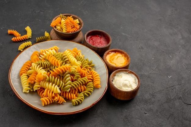 Vorderansicht gekochte italienische pasta ungewöhnliche spiralnudeln mit gewürzen auf dunklem raum