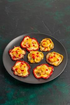Vorderansicht gekochte paprika zum mittagessen in teller auf dunkelgrüner oberfläche