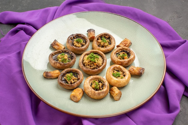 Vorderansicht gekochte pilze innerhalb des tellers auf violettem gewebe und auf dunklem hintergrundgericht mahlzeit kochen von pilzen abendessen