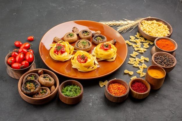 Vorderansicht gekochte pilze mit teignudeln und gewürzen auf dunklem tischmahlzeitgericht