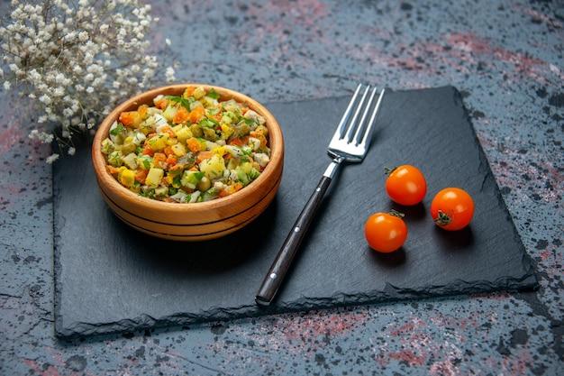 Vorderansicht gekochter gemüsesalat mit gabel auf blauem hintergrund