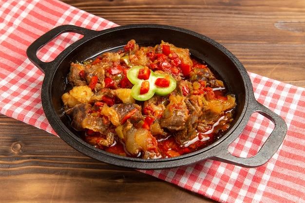 Vorderansicht gekochtes gemüsemehl einschließlich gemüse und fleisch innen auf braunem schreibtisch
