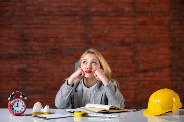 Vorderansicht gelangweilt ingenieurin, die hinter ihrem arbeitsplatz sitzt