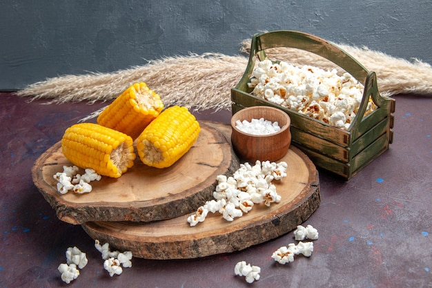 Vorderansicht gelbe hühneraugen geschnitten mit popcorn auf der dunklen oberfläche mais-snack-pflanzen-baumöl