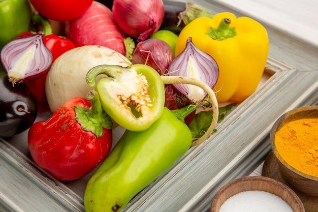 Vorderansicht gemüsezusammensetzung mit gewürzen auf weißem hintergrund farbfoto gemüse gesundes leben salatmahlzeit reif