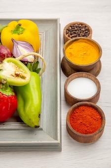 Vorderansicht gemüsezusammensetzung mit gewürzen auf weißem hintergrund farbfoto gemüse reif gesundes leben salatmahlzeit