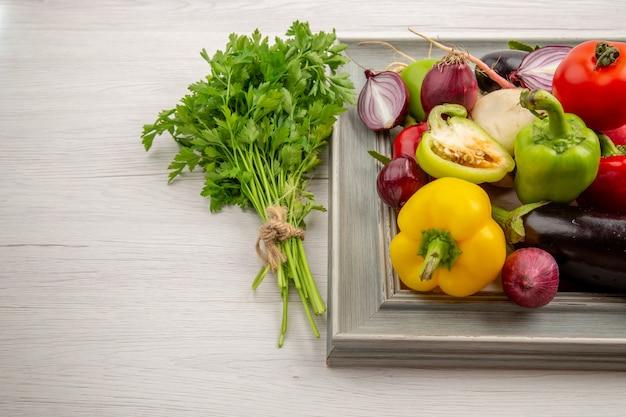 Vorderansicht gemüsezusammensetzung mit gewürzen und grüns auf weißem hintergrund farbfoto gemüse gesundes leben salatmahlzeit reif