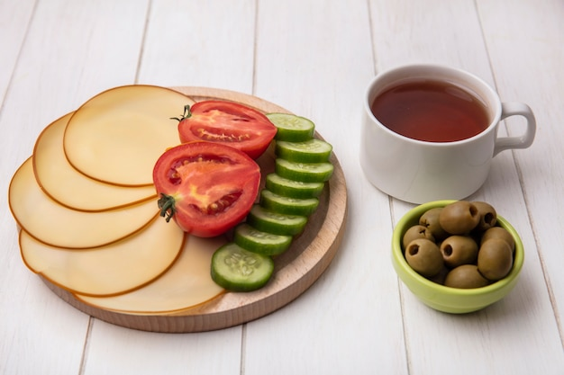 Vorderansicht geräucherter käse mit tomatengurken auf einem stand mit oliven und einer tasse tee auf einem weißen hintergrund