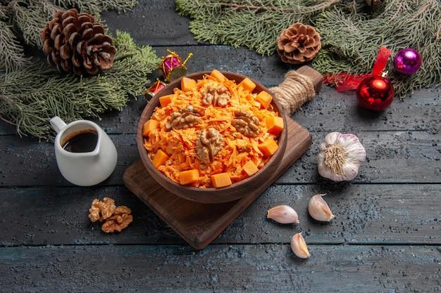 Vorderansicht geriebener karottensalat mit walnüssen auf dunkelblauem hintergrund gesundheit salat farbe diät lebensmittel nuss