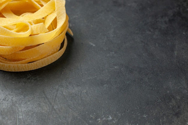 Vorderansicht gerolltes teigstück auf dunklem hintergrund teig mahlzeit essen pasta dunkelheit küche freiraum pasta