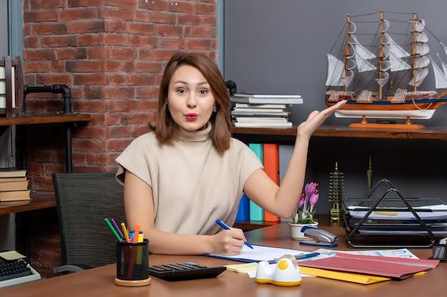Vorderansicht geschäftsfrau, die auf etwas zeigt, das am schreibtisch im büro sitzt
