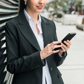 Vorderansicht-geschäftsfrau, die ihr smartphone prüft