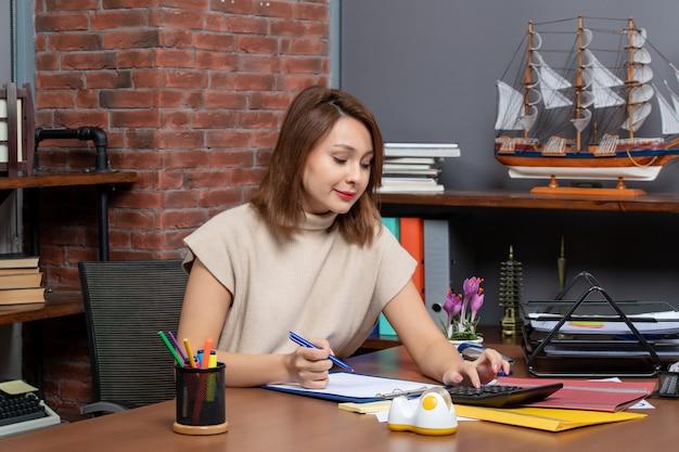 Vorderansicht geschäftsfrau mit taschenrechner am schreibtisch im büro sitzen