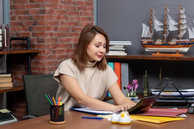 Vorderansicht geschäftsfrau sitzt am tisch im büro