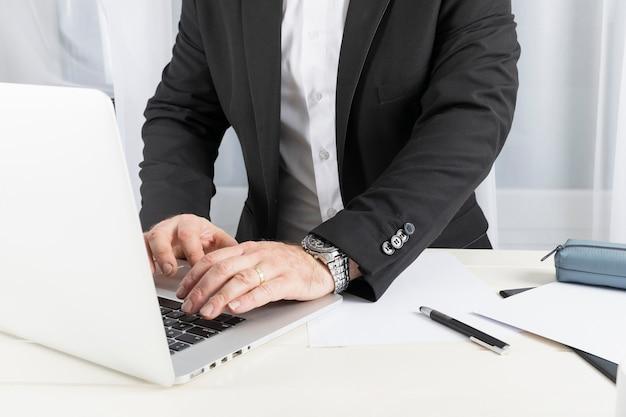 Vorderansicht-geschäftsmann, der an seinem laptop arbeitet