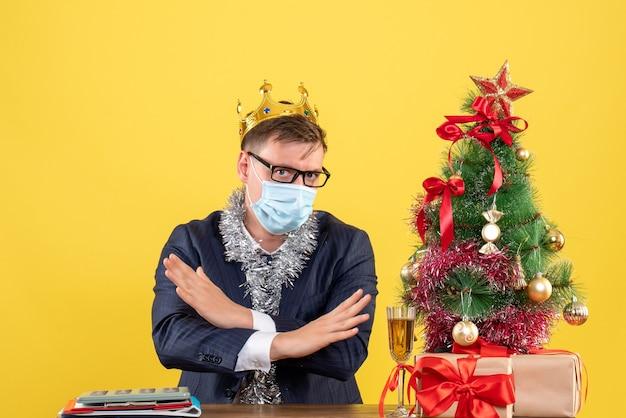 Vorderansicht-geschäftsmann, der hände kreuzt, die am tisch nahe weihnachtsbaum sitzen und auf gelbem hintergrund präsentieren