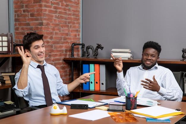 Vorderansicht geschäftsverhandlungen zwei zufriedene geschäftsführer bei der arbeit im büro