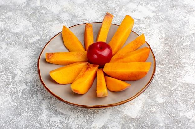 Vorderansicht geschnittene frische pfirsiche innerhalb platte auf dem hellen weißen hintergrund.