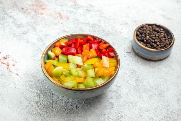 Vorderansicht geschnittene paprika mit gewürzen auf weißem raum