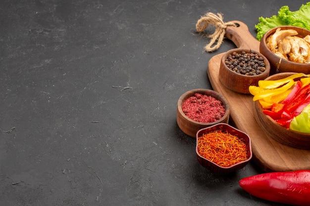 Vorderansicht geschnittene paprika mit gewürzen und dunklem brot auf dunklem raum