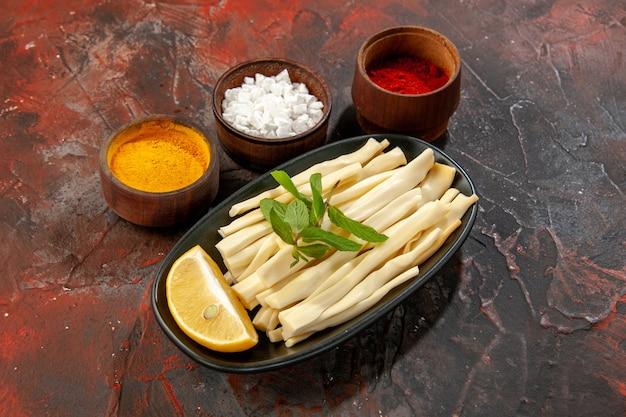 Vorderansicht geschnittener käse mit zitronenstück und gewürzen auf dunkler essenssnack-fotofarbe